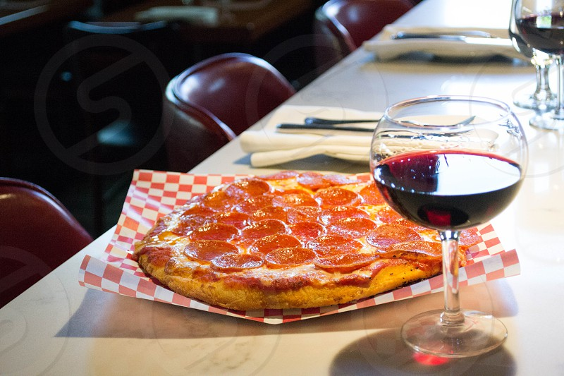 snifter wine glass beside sliced pepperoni pizza photo