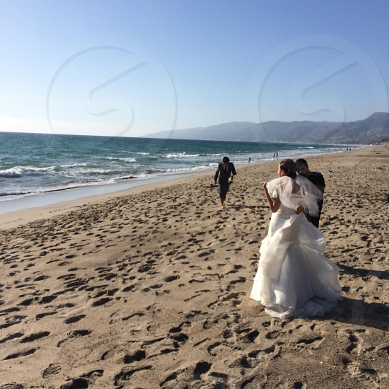 woman in white bridal gown beside man in black near shore photo