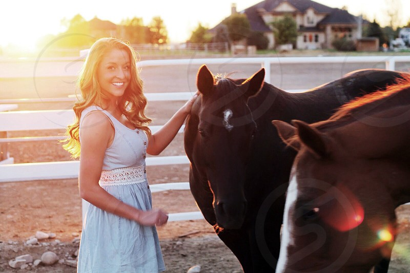 woman with curly long hair in white sleeveless gown standing with two brown horses in sunlight photo
